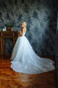 Een mooie bruid in een heel mooie lange jurk met een trein staat bij het raam.