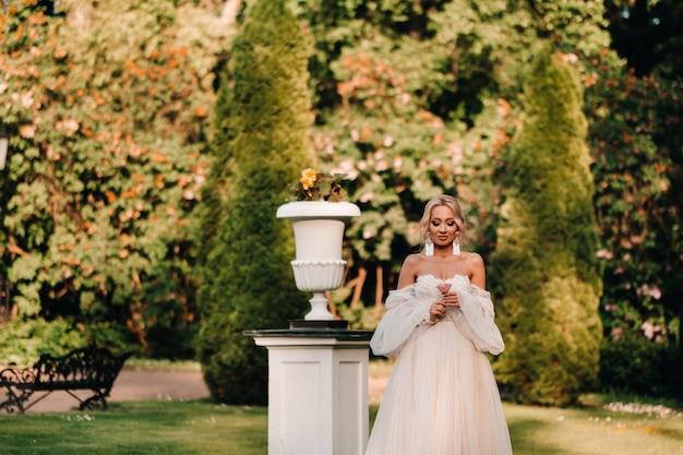 Een mooie bruid in een luxe trouwjurk houdt een roos en groen op een groene natuurlijke achtergrond. portret van een gelukkige bruid in een witte jurk, glimlachend tegen de achtergrond van een park.