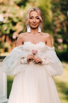 Een mooie bruid in een luxe trouwjurk houdt een roos en groen vast