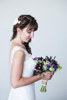 Een mooie bruid met een europese uitstraling in een sneeuwwitte jurk poseert in het interieur. de bruid wacht op de huwelijksceremonie.