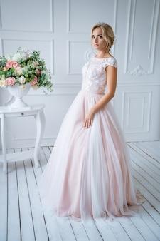 Een mooie bruid met haar en make-up staat in een delicate roze trouwjurk in een licht decor met bloemen