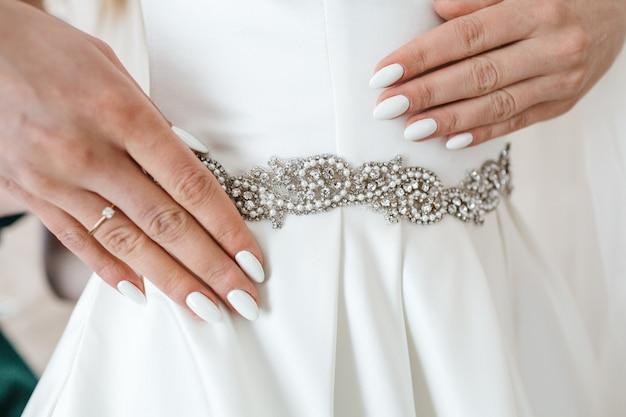 Een mooie bruid probeert haar jurk