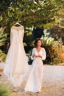 Een mooie bruid staat naast een trouwjurk met een kopje thee in een boudoir-outfit naast een villa in italië. ochtend van de bruid in toscane.