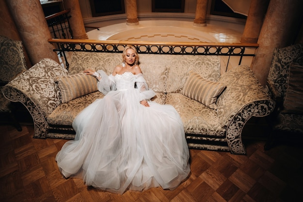 Een mooie bruid zit op een luxe bank