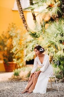 Een mooie bruid zit op een stoel en lacht in haar ondergoed en kamerjas naast een villa in italië. ochtend van de bruid in toscane.