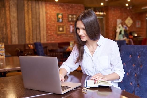 Een mooie brunette blogger met lang goed verzorgd haar zit in een café. een jonge vrouw blogt op internet over het leven, vertelt ze abonnees over hard werken en geweldige reizen.