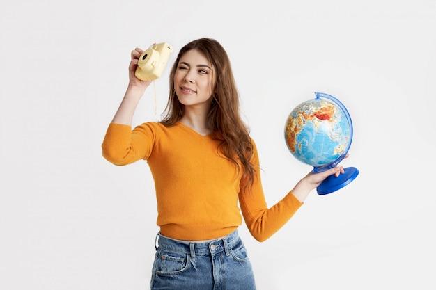 Een mooie brunette in een gele trui houdt een wereldbol in haar handen en kijkt in de zoeker van de camera. recreatie, reizen, toerisme. ruimte voor tekst