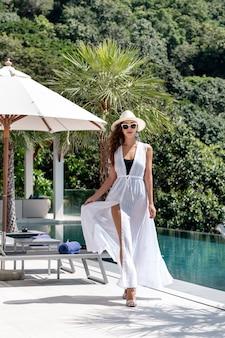 Een mooie brunette in een witte zomerjurk en witte hoed staat bij het zwembad