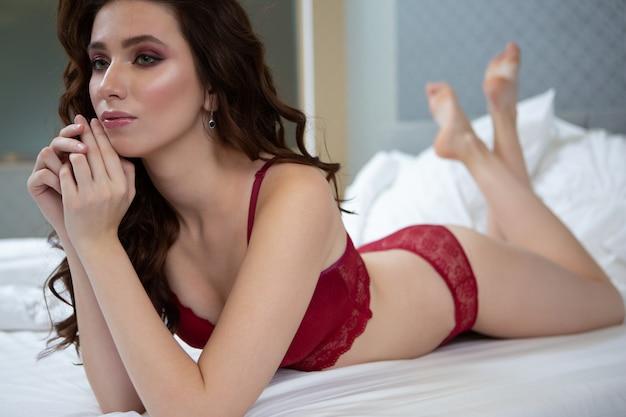 Een mooie brunette in elegant rood slipje ligt op het spreidbed en droomt van iets