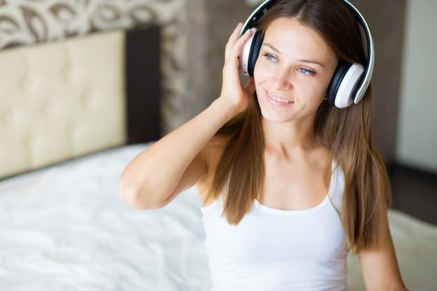 Een mooie brunette meid met een koptelefoon in de slaapkamer