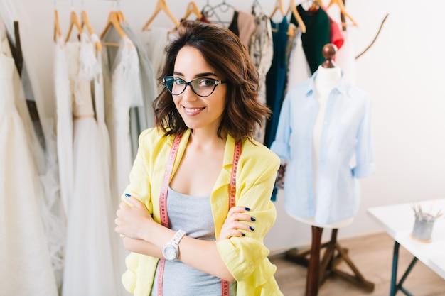 Een mooie brunette meisje in een grijze jurk en gele jas staat in de buurt van kleding in de studio van de werkplaats. ze heeft een plakband om haar nek.