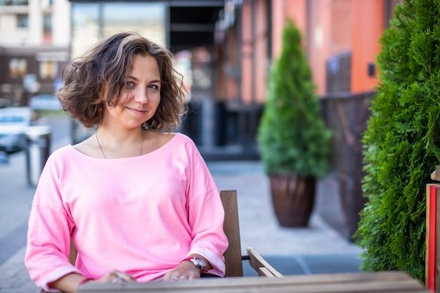Een mooie brunette meisje in trendy kleding zit in een zomerterras.