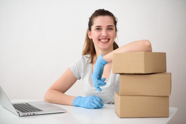 Een mooie brunette met een glimlach, leunend op drie kartonnen dozen, zit in siliconen handschoenen voor een laptop.
