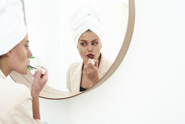 Een mooie brunette staat in een pak in de badkamer en schildert 's ochtends voor het werk haar lippen met matte donkere lippenstift.