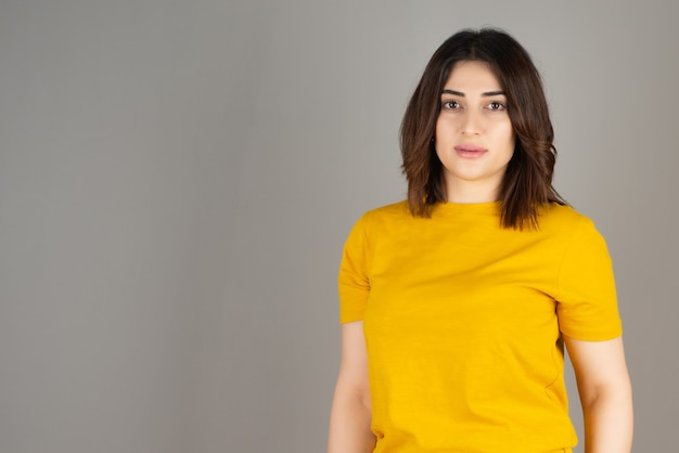 Een mooie brunette vrouw in geel t-shirt staat en poseert tegen een grijze muur