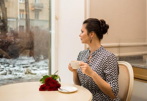 Een mooie brunette vrouw met een kopje koffie en rozen zit aan een tafel in een café en kijkt uit het raam