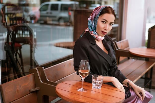 Een mooie brunette vrouw met lichte make-up zit in een café op straat met een glas wijn