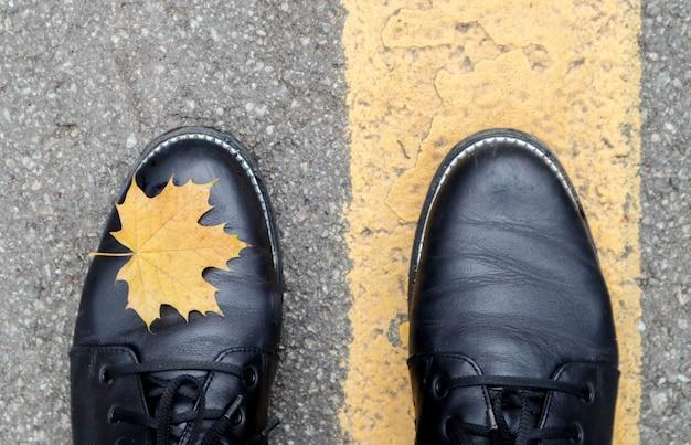 Een mooie combinatie van een geel esdoorn herfstblad naast de gele wegmarkeringen en de benen van een meisje met zwarte laarzen in het park. herfst concept, mooie achtergrond met kopie ruimte.