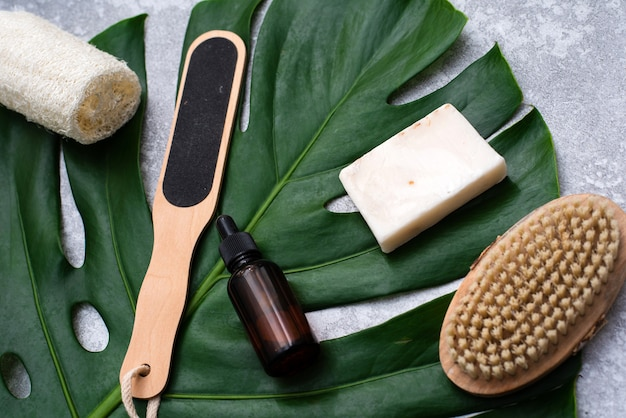 Een mooie compositie met olie, zeep en noten. flessen met cosmetische spaproducten op een palmbladachtergrond, bovenaanzicht. schoonheidssalon procedures concept.