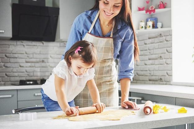 Een mooie dochter met haar moeder koken in de keuken
