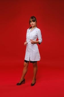 Een mooie dokter meisje houdt een reflex hamer en lacht naar de camera geïsoleerd op een rode achtergrond.