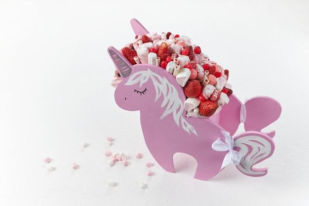 Een mooie eenhoorn vormige doos gevuld met rijpe aardbeien en snoep