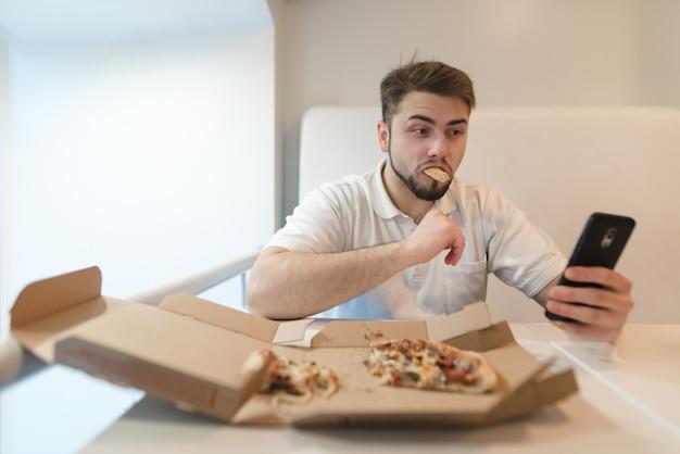 Een mooie en grappige man eet een pizza uit de doos en pakt zijn telefoon op. selfies met pizza