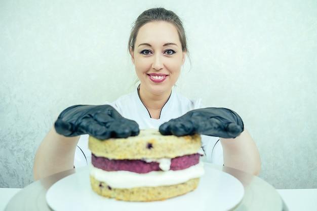 Een mooie en lachende vrouw banketbakker in zwarte handschoenen en een wit werkuniform bakt een taart in de keuken. banketbakker, cake, koken.
