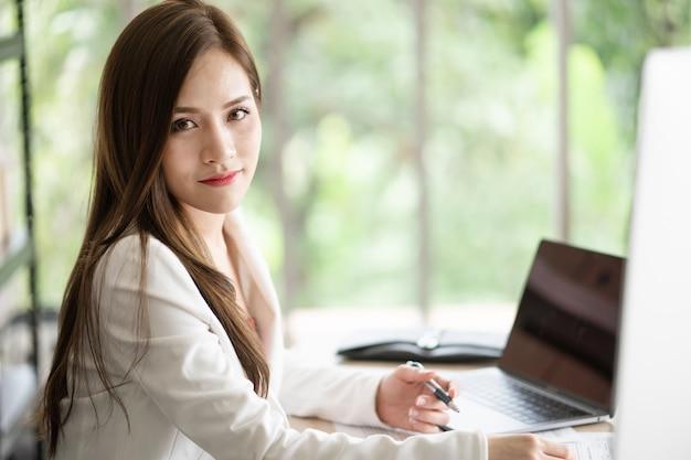 Een mooie en slimme werkende vrouw zit aan haar bureau op kantoor.