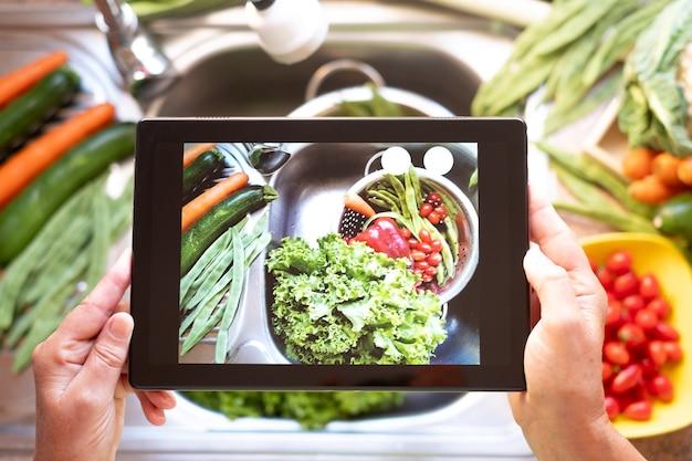 Een mooie foto met de digitale tablet op een stalen spoelbak vol verse en rauwe groenten