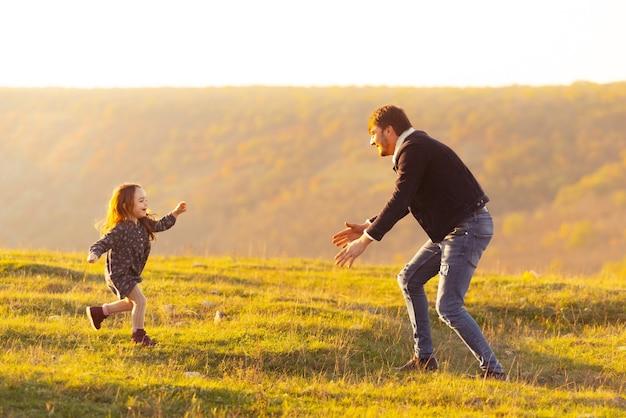 Een mooie foto van een dochter die vaders handen tegenkomt op het veld