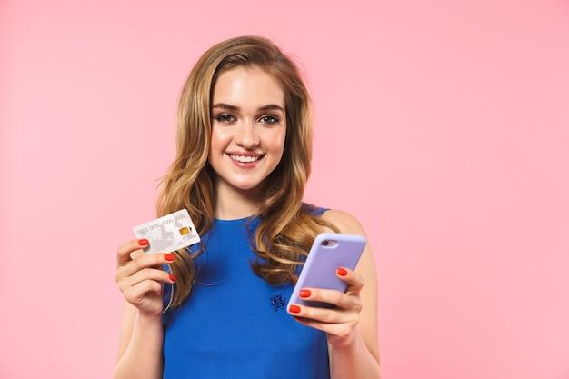 Een mooie gelukkige jonge mooie vrouw die zich voordeed over een roze muur met een creditcard die een mobiele telefoon gebruikt
