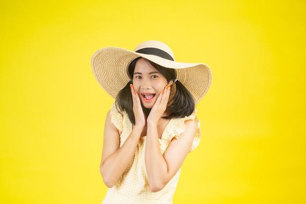 Een mooie, gelukkige vrouw die een grote hoed draagt die opgewektheid op een geel toont.