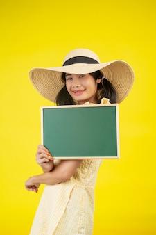 Een mooie, gelukkige vrouw die een grote hoed draagt en een groen bord op een geel houdt.