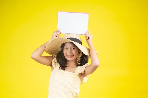 Een mooie, gelukkige vrouw die een grote hoed draagt en een wit boek op een geel houdt.