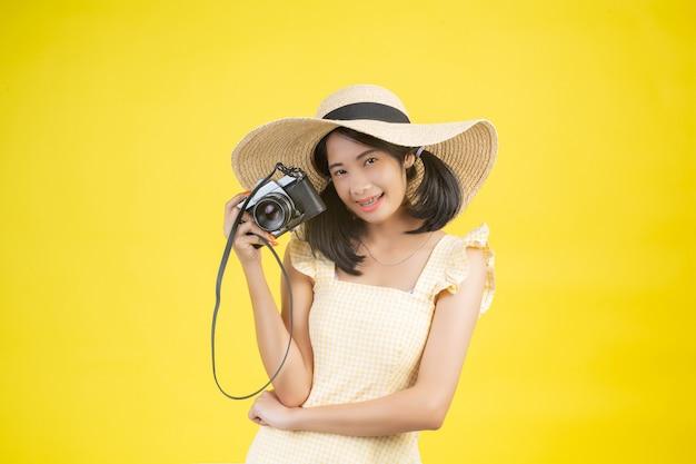 Een mooie, gelukkige vrouw die een grote hoed en een camera op een geel draagt.