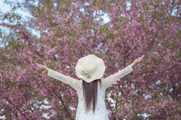 Een mooie, gelukkige vrouw stond buiten met een open geest en keek naar de lucht.