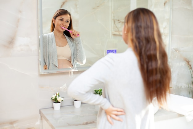 Een mooie gelukkige zwangere vrouw in huiskleren poetst haar tanden voor een spiegel in een lichte badkamer. levensstijl. ochtend- en avondroutine. hygiëne. gezondheidszorg. hoge kwaliteit foto