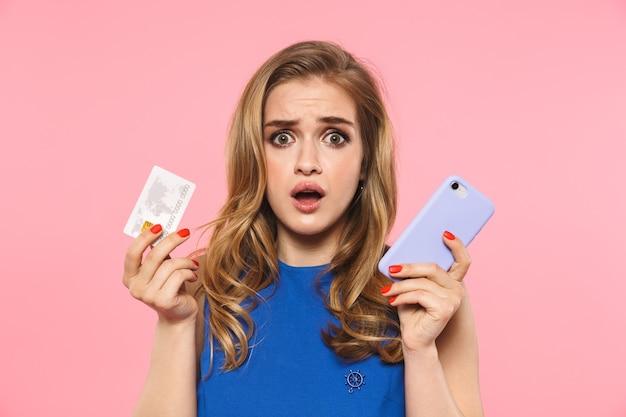 Een mooie geschokte, droevige jonge mooie vrouw die zich geïsoleerd over een roze muur met een creditcard met behulp van mobiele telefoon poseert