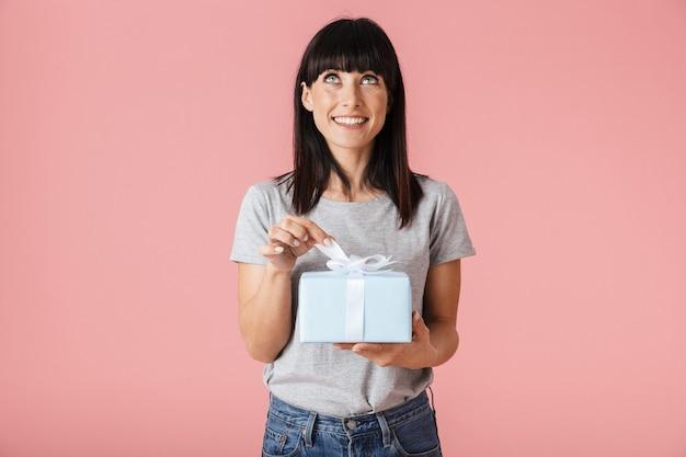 Een mooie geweldige opgewonden gelukkige vrouw poseren geïsoleerd over licht roze muur muur met huidige geschenkdoos.