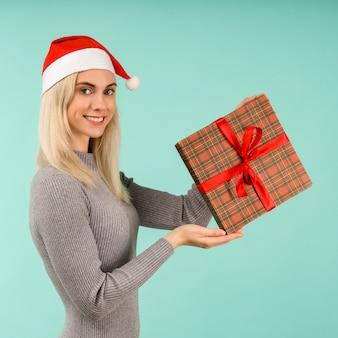 Een mooie glimlach sexy meisje in new year's hoed en grijze jurk, geschenken in handen te houden