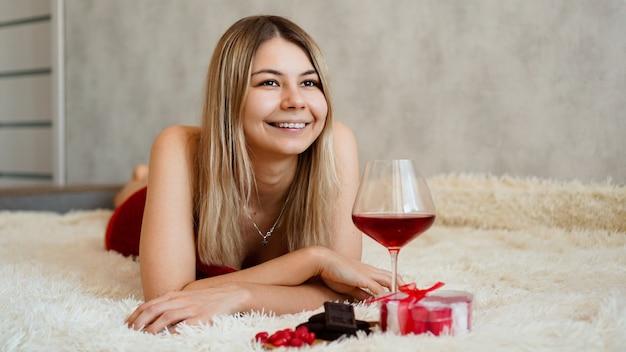 Een mooie glimlachende blonde ligt in bed. valentijnsdag ochtend. een glas wijn, chocolade, snoep en een cadeautje naast het meisje. gelukkige verliefde ochtend