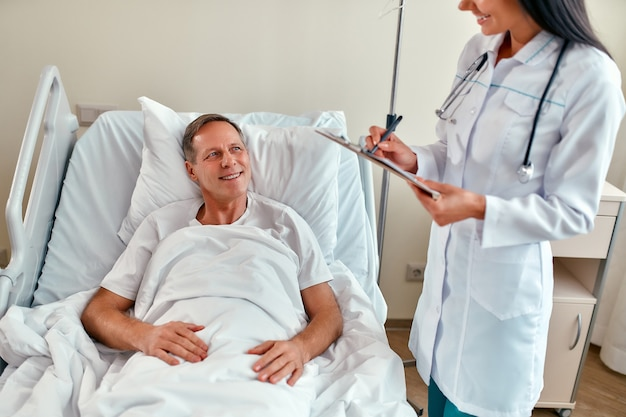 Een mooie glimlachende jonge verpleegster maakt aantekeningen op de kaart van een patiënt en onderzoekt hem in een moderne ziekenhuisafdeling.