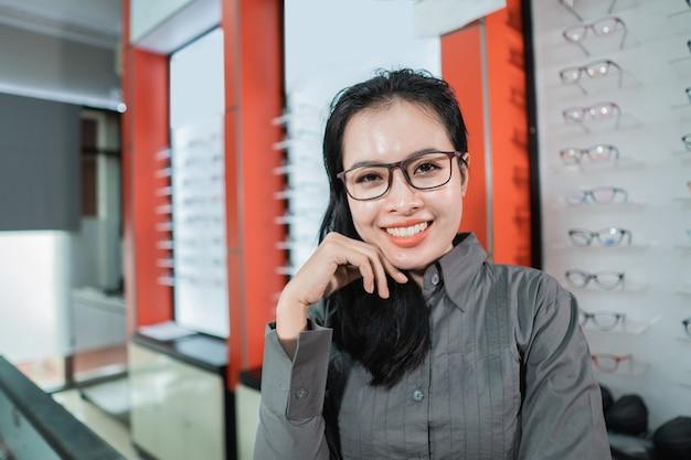 Een mooie glimlachende vrouw die een bril draagt tegen de achtergrond van een lenzenvloeistofrek in de winkel van een opticien