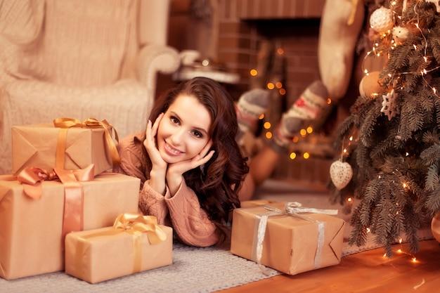 Een mooie glimlachende vrouw in een warme gebreide trui en sokken die dichtbij mooie kerstbomen en giften, het binnenland van het nieuwjaarhuis liggen