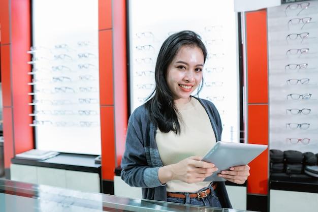 Een mooie glimlachende vrouw is in een oogkliniek met een lenzenvloeistofproductcatalogus tegen de achtergrond van een lenzenvloeistofvenster