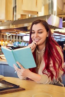 Een mooie glimlachende vrouw met rood haar werkt op afstand in een café met een notitieboekje in haar hand
