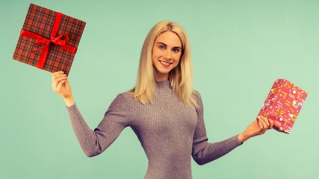 Een mooie glimlachvrouw in een grijze jurk, houdt geschenken in handen. viering van kerstmis of nieuwjaar