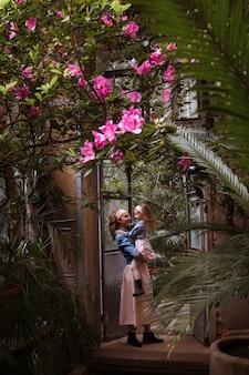 Een mooie heldere jonge vrouw met een dochtertje in haar armen, in bloeiende bloem, glimlachend. het concept van een warme relatie in de familie, weelderige bloei.