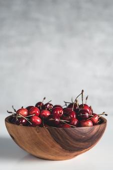 Een mooie houten vaas gevuld met bessen. bord met kersen. veganistisch, eco, boerderijproduct, biologisch voedsel